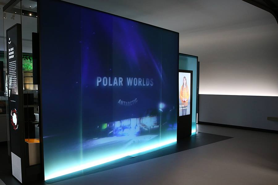 a blue screen with the words polar worlds in a grey modern room