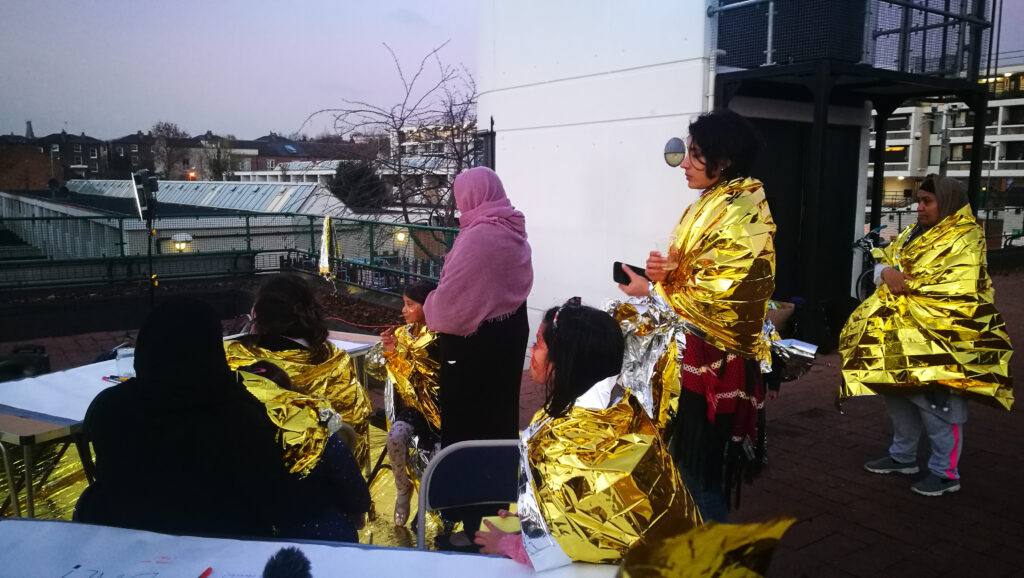 photograph of women in gold heat blankets participating in an activity on a rooftop
