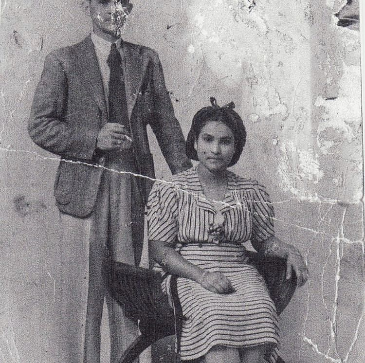 An old black and white photograph of a woman sitting on a chair and a man in a suit standing behind her.