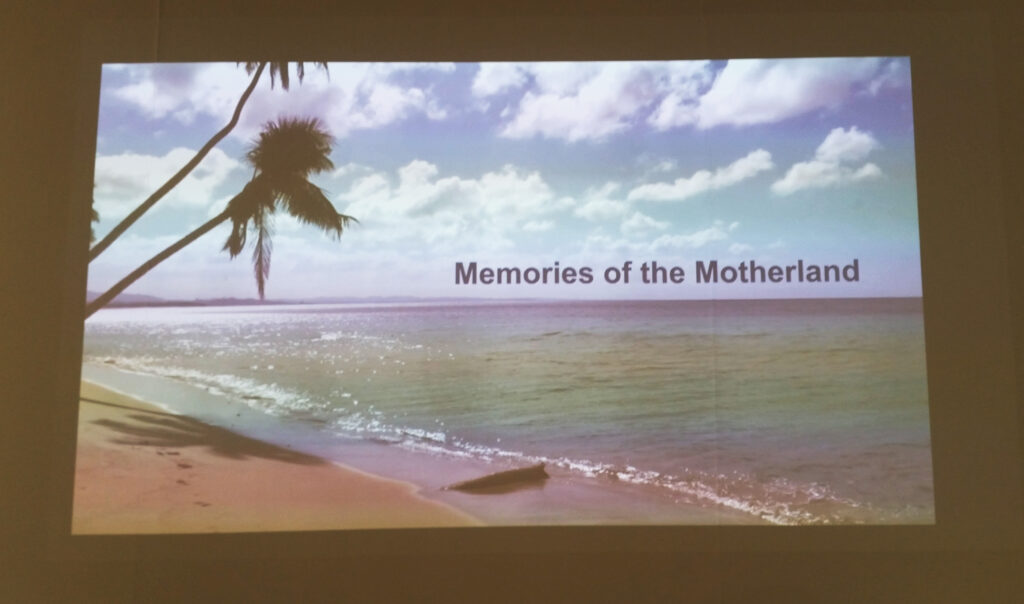 a projected image of sea on a beach with a palm tree and the worlds Memories of Motherland.