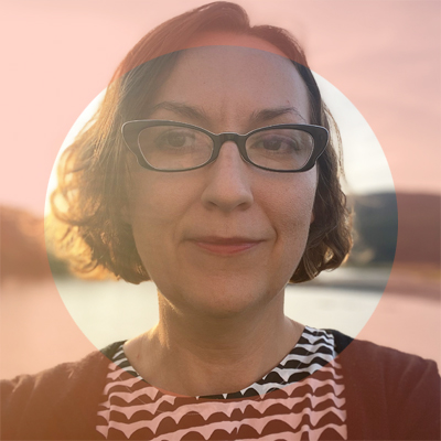 photograph portrait of a woman wearing glasses with mid-length hair in a circular peach pink frame
