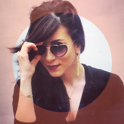 photograph of a woman with dark hair wearing heart shaped sunglasses framed in a peach coloured circle