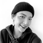 black and white portrait of a woman with short hair wearing a dark hat and hoodie.