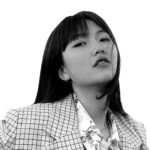 black and white photograph of a woman with long dark hair wearing a checked blazer