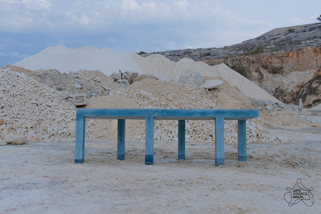 image of a blue concrete table-like structure in a quarry with piles of stones and sand behind it.