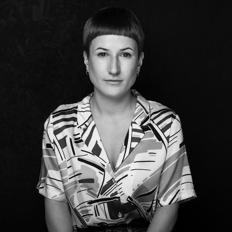 black and white portrait photo of Anna Horvath, wearing a brush stroke pattern shirt and short brown hair.