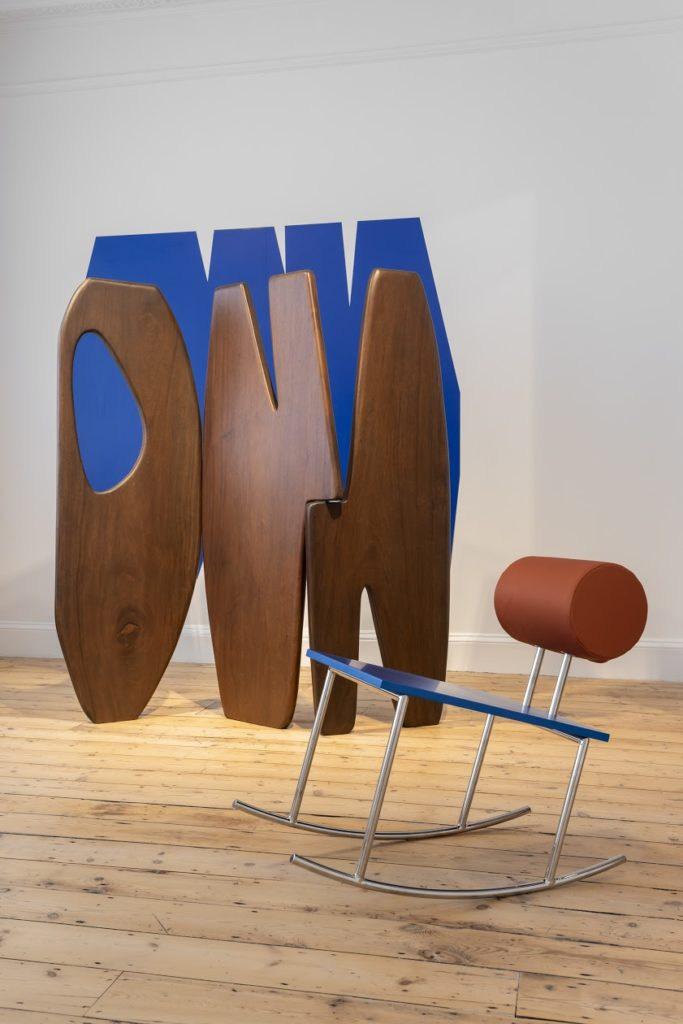 image of Anna Horvath's design for a rocking chair with metal legs, juxtaposed with a wooden organic shaped sculptural installation.