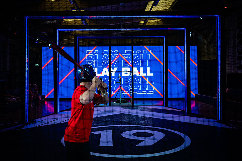 image of a man in a red t-shirt holding a baseball bat wearing a helmet, in front of an interactive bluescreen with the words 'play ball' displayed on it white capital letters.