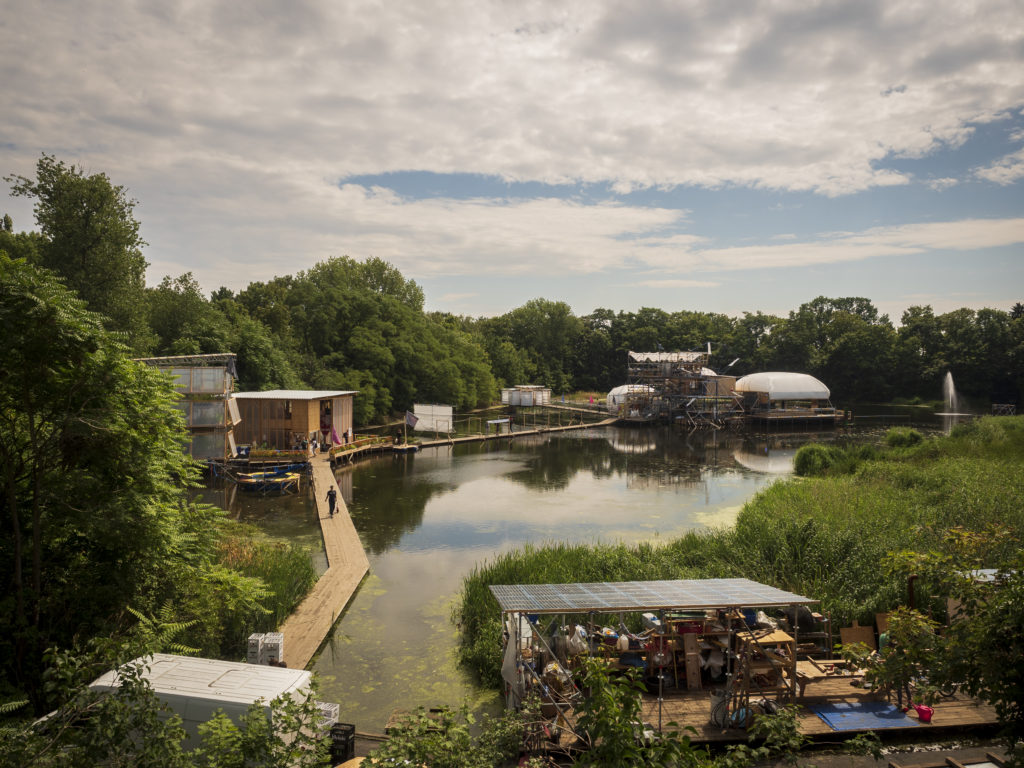 image of the floating university in Berlin's buildings floating on the water surrounded by trees.