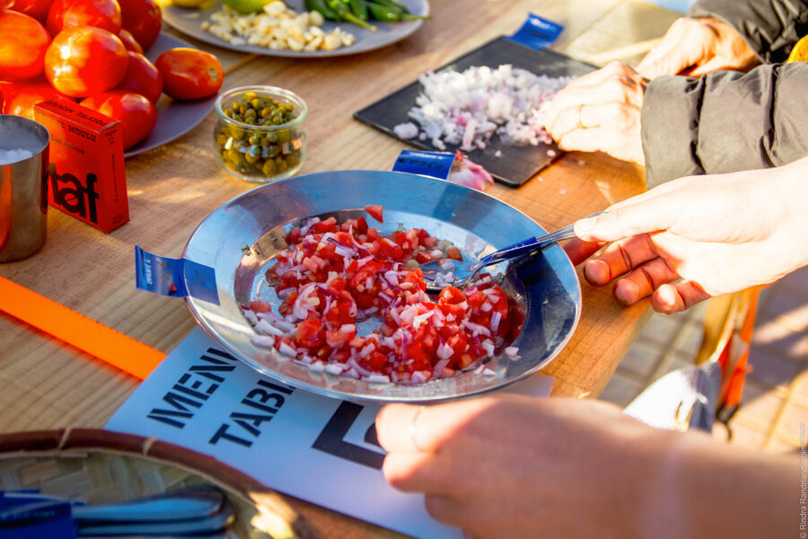 image of a person's hands picking up a metal bowl of red chopped vegetables with a spoon in it.