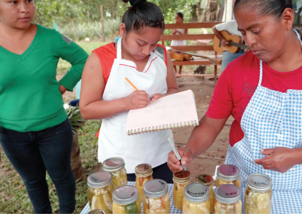 Mobile experimental kitchen at the border of the Lacandona Jungle, Mexico, showing a man in a checked blue and white apron writing on filled jar lids.