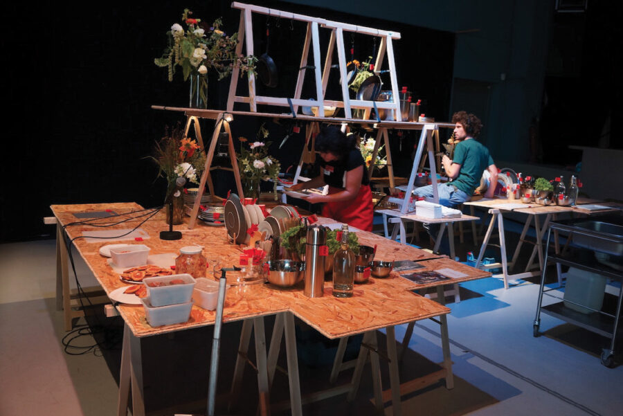 image of people working in the mobile kitchen made from wooden tressle tables holding plates and kitchenware, at the V2 Centre.