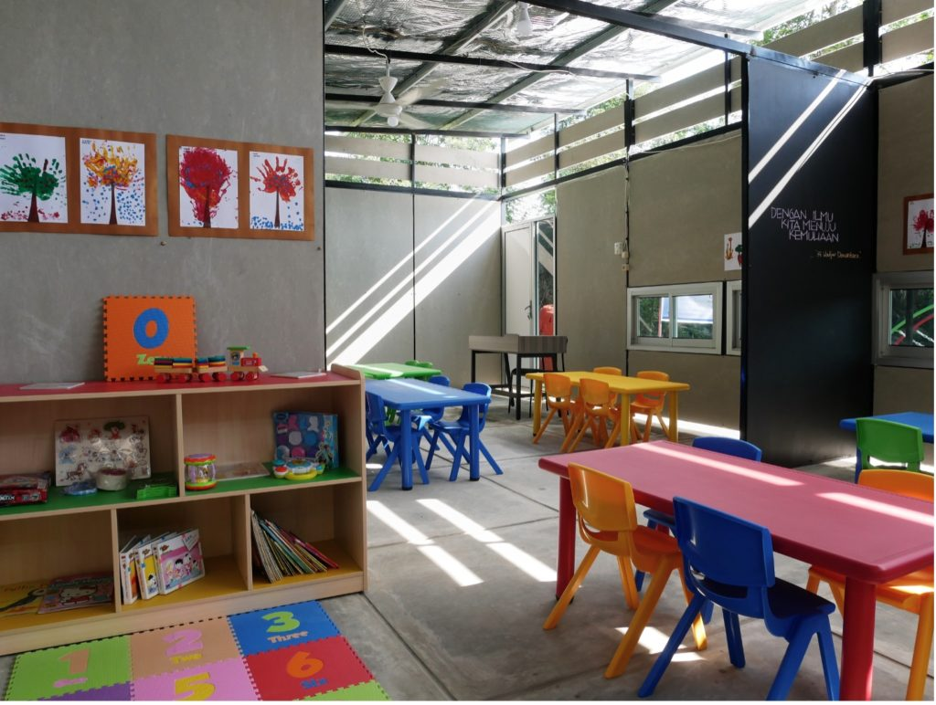 Image showing the interior of a modular built classroom with bright coloured tables and chairs, bookshelves holding educational objects.