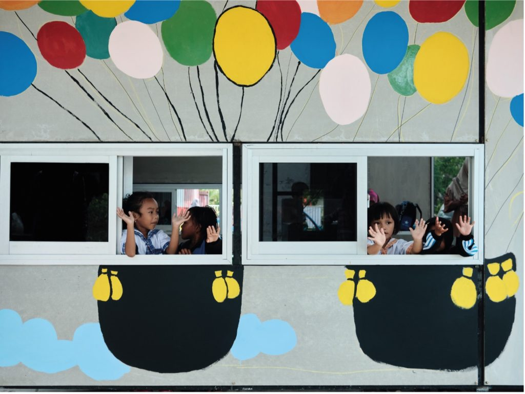 Image of children looking out the window and waving at one of the  Sekolah Indonesia Cepat Tanggap schools.