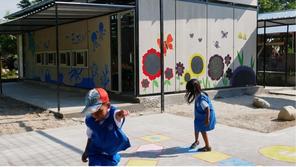 Image of children playing outside one of the Sekolah Indonesia Cepat Tanggap modular schools, with the grey wall of the school behind them decorated with large painted flower illustrations.