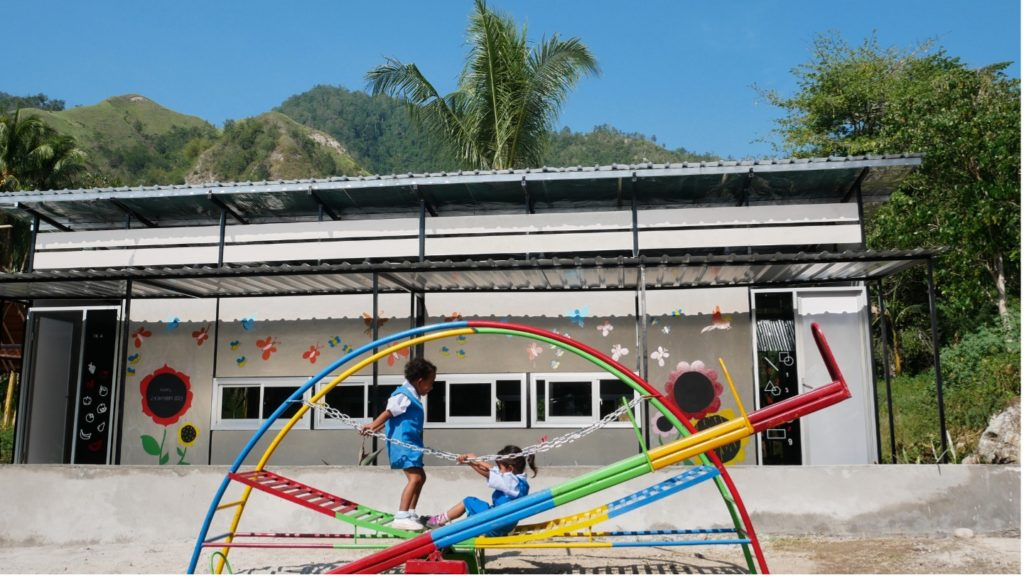 Image of children playing on a bright coloured metal play frame outside one of the Sekolah Indonesia Cepat Tanggap schools.