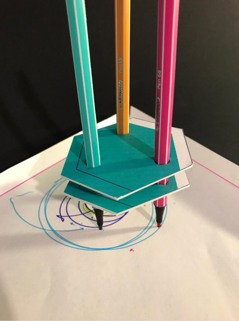 Image of the 'art robot' made from a perforated cardboard base with pens inserted in it, drawing on white paper.