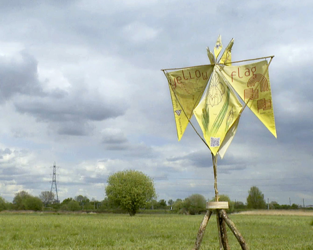 A wooden tripod structure with yellow graphics printed on linen flags hanging in the shape of an iris in front of a green field and sky.