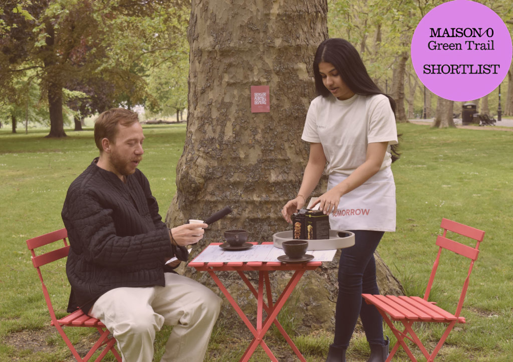 a bearded man sitting at a pink fold out table under a tree holding a cup of coffee whilst a woman with dark hair standing up pours coffee into a cup.